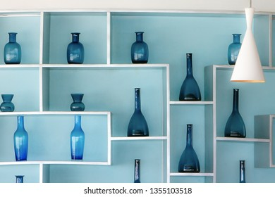 Retro style blue glass bottles in a beautiful arrangement on shelves attached to a light blue wall.