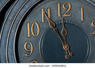 Retro style clock with gold like numbers showing five minutes to midnight.