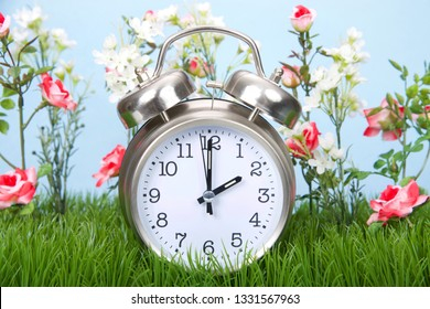 Retro style clock sitting in green grass with flowers representing daylight savings spring forwards.