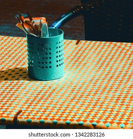 Retro style diner. Toned photo. Outdoor cafe terrace with checkered tablecloth covering table and utensil setting in metal pot. Wicker chair on sidewalk pavement. Vintage background.