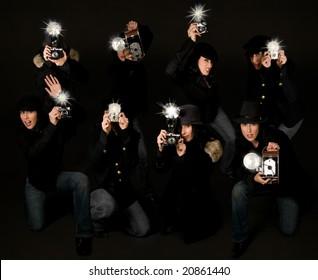 Retro style female paparazzi press photographers with vintage cameras