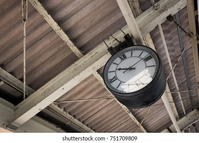 Retro style hanging clock on the ceiling of a station.