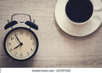 retro style image of alarm clock showing seven fifty five with cup of coffee on the wooden background. top view.