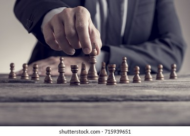 Retro style image of a businessman playing a game of chess on an old wooden table in a close up view of his hand moving a piece conceptual of strategy, planning and skill.