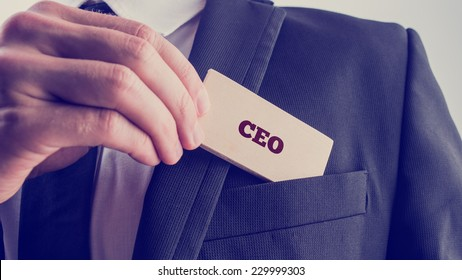Retro style image of a businessman showing a wooden card reading - CEO - as he withdraws it from the pocket of his suit jacket.