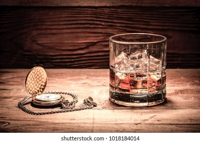 A retro style image of a glass of liquor with ice and a pocket watch on wood.