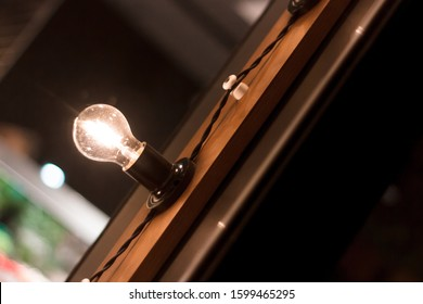 Retro style light bulb in one of the farm shops. Background with burning lights. Wooden window frame with a design of incandescent lamps in a black cartridge in a vintage style. Tesla lamp close-up.