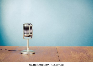 Retro style microphone on table in front aquamarine wall background