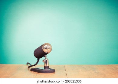 Retro style microphone on table front mint green background