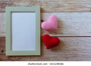Retro style pastel green frame with pink and red hearts on wooden white floor. Minimal and simple love photo concept. Copy space for text. Love is all around.