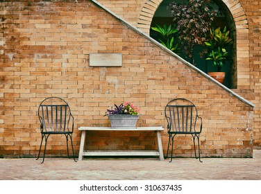 Retro style photo of chairs and wooden table with  brick wall in backyard
