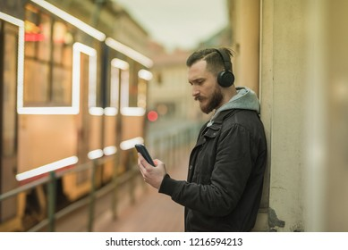 A retro style photo of a hipster man while checking his smartphone in an urban environment.