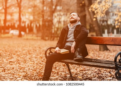 A retro style photo of a young hipster man sitting on a bench with a book and daydreaming.