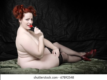 Retro style picture overweight woman with red lollipop. Low key studio shot with black background.