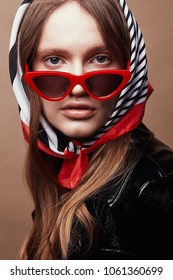 Retro style portrait of amazing young woman in red cat eye sunglasses and retro headscarf with black, white and red stripes