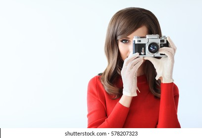 Retro style portrait of young beautiful woman taking photo with camera on white background with copy space