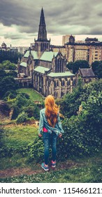 Retro Style Redhead Teenage Girl Looking Out Over Glasgow Cathedral And Skyline With A Rainy Sky