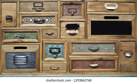 Retro style rustic chest of drawers with drawers of different shapes and colors.