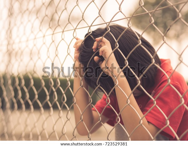 Retro style sad boy behind fence mesh netting. Emotions concept - sadness, sorrow, melancholy.