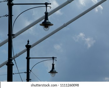 retro style street lamp heads by suspension bridge sctructural cables under blue sky with cluds
