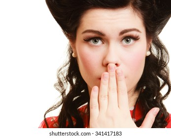 Retro style. Surprised woman covering mouth with hand gesture isolated on white. Portrait of scared pinup brunette girl.