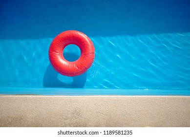Retro style swimming pool with a vivid red inflatable swim ring