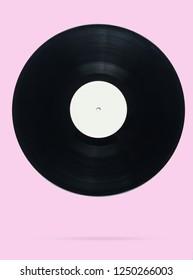 Retro style vinyl record on pink pastel background, minimalism. Photo with shadow