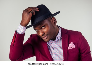 Retro style well dressed African american business man model in red suit and black hat in studio on white background