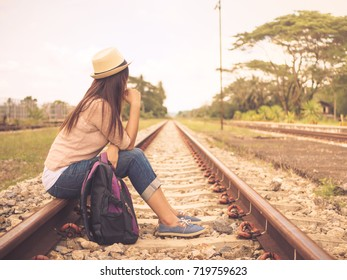 Retro style of woman with backpack on the railway platform. Travel and vacation concept.