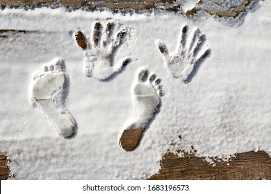 retro style wooden background. The first snow fell on it. Left human footprints of hands and feet.