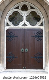 Retro style wooden door with stained glass decorations in the arch area. The architectural feature belongs to the Baptist Church located in Church Street in the downtown district