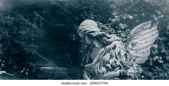 Retro styled ancient statue of sad angel with wings against dark background