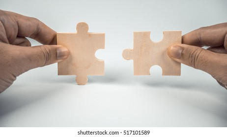 Retro styled or retro color finger holding pieces of blank wooden puzzle. Slightly de-focused and close-up shot. Copy space.