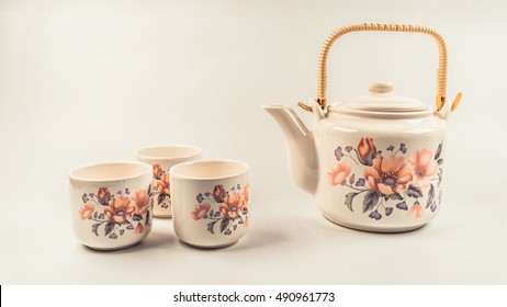 Retro styled or retro color traditional japanese or chinese oriental ceramic tea pot with floral motif. Isolated on empty background. Slightly de-focused and close-up shot. Copy space.