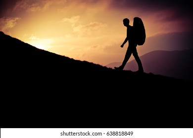 Retro Styled Design Of A Silhouetted Young Man Hiking Up A Steep Hill At Sunset