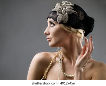 retro styled girl in black hat and white beads