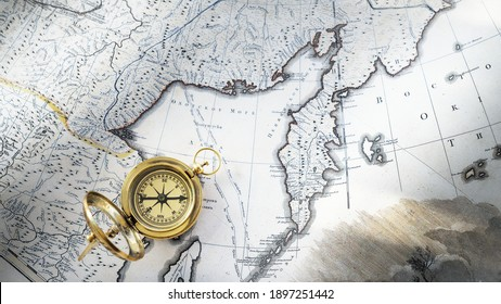 Retro styled golden compass (sundial) and old white nautical chart close-up. Vintage still life. Sailing accessories. Travel, navigation, history, collecting, hobby. Panoramic image, copy space