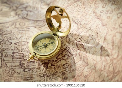Retro styled golden compass (sundial) and old white nautical chart. Vintage still life. Sailing accessories. Travel, navigation, collecting, 3D modeling, souvenir, gift, graphic resources, copy space