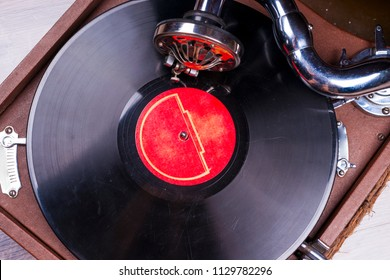 Retro styled image of a collection of old vinyl record lp's with sleeves. Browsing through vinyl records collection. Music background. Copy space. Old gramophone player with vinyl record. op view.
