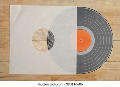 Retro styled image of a collection of old vinyl record lp's with sleeves on a wooden background