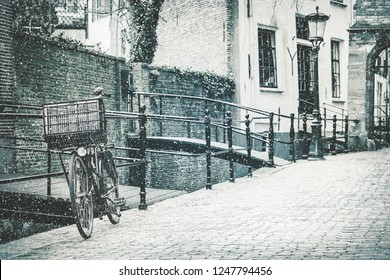 Retro styled image of the Dutch city of Gouda with a bicycle in front in winter