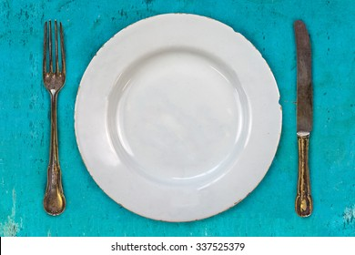 Retro styled image of an empty dinner plate with fork and knife on a blue background