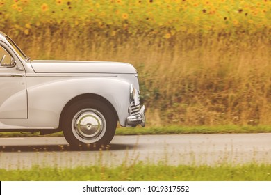 Retro styled image of a fifties car driving by a field with blooming sunflowers