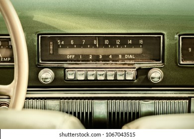 Retro styled image of an old car radio inside a green classic car - Shutterstock ID 1067043515