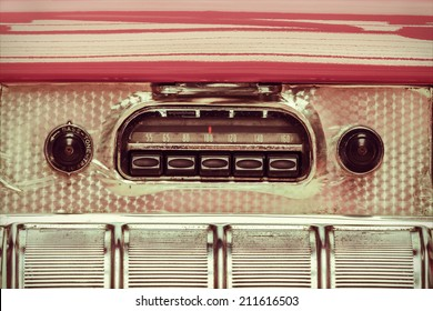 Retro styled image of an old car radio inside a pink classic car