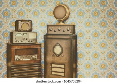 Retro styled image of old radio's in front of a retro wallpaper with flower pattern