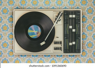 Retro styled image of an old record player on top of flower wallpaper