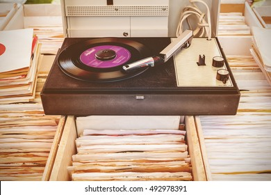 Retro styled image of an old turntable on top of used vinyl lp records