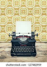 Retro styled image of an old typewriter on a wooden floor with vintage wallpaper behind it