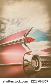 Retro styled image of the rear end of a pink classic car